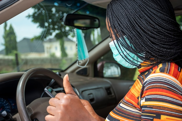 Young black woman using her phone while sitting in a car, wearing a face mask, giving a thumbs up gesture
