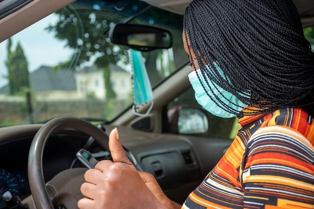 젊은 흑인 여성은 차에 앉아 얼굴 마스크를 쓰고 엄지손가락을 치켜드는 제스처를 취하는 동안 전화를 사용합니다.