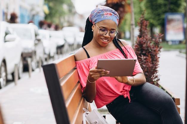 路上でタブレットコンピューターを使用して若い黒人女性