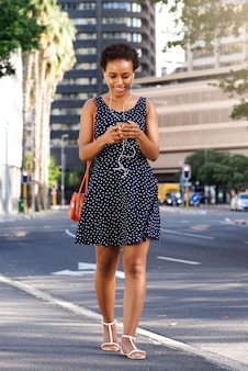 Young black woman walking in city with smart phone and purse