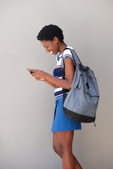 Young black woman walking and using cell phone on gray background
