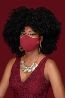 Молодая темнокожая женщина в красной маске и защите от covid-19 во время рождественской вечеринки изолирована на красном фоне