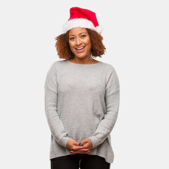 Young black woman wearing a santa hat cheerful with a big smile