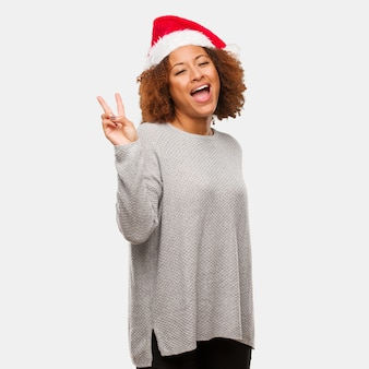 Young black woman wearing a santa hat doing a gesture of victory