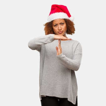 Young black woman wearing a santa hat doing a timeout gesture
