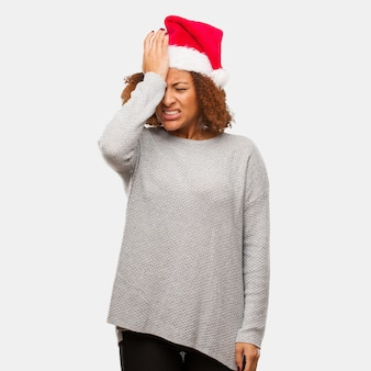 Young black woman wearing a santa hat forgetful, realize something