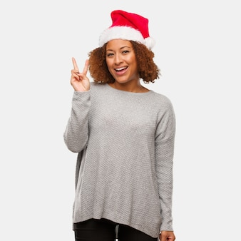 Young black woman wearing a santa hat fun and happy doing a gesture of victory