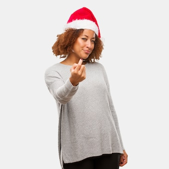 Young black woman wearing a santa hat inviting to come
