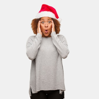 Young black woman wearing a santa hat surprised and shocked