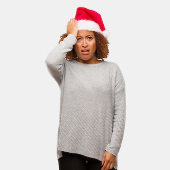 Young black woman wearing a santa hat worried and overwhelmed