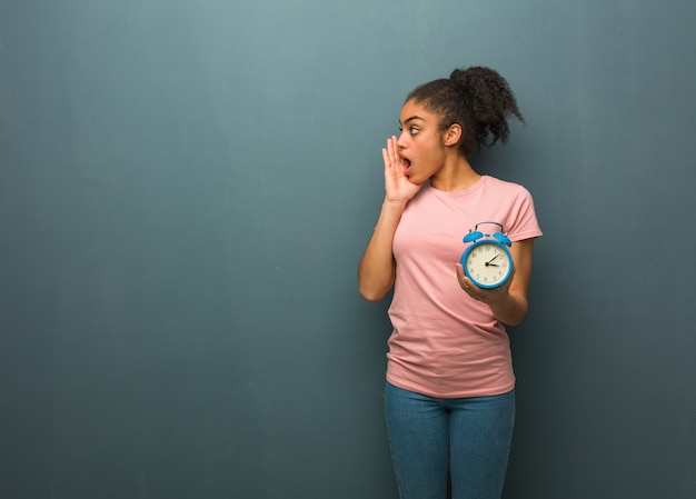 Young black woman whispering gossip undertone. she is holding an alarm clock.