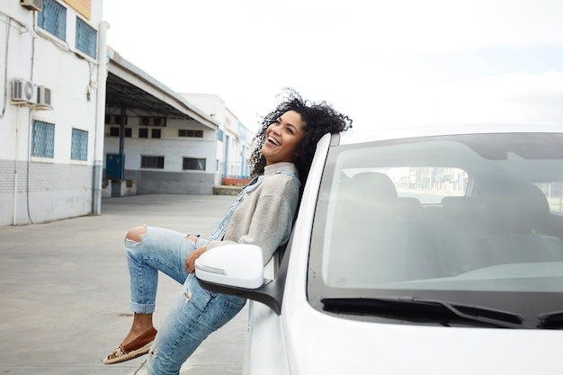 Young black woman with afro hair laughing and enjoying leaning on her car