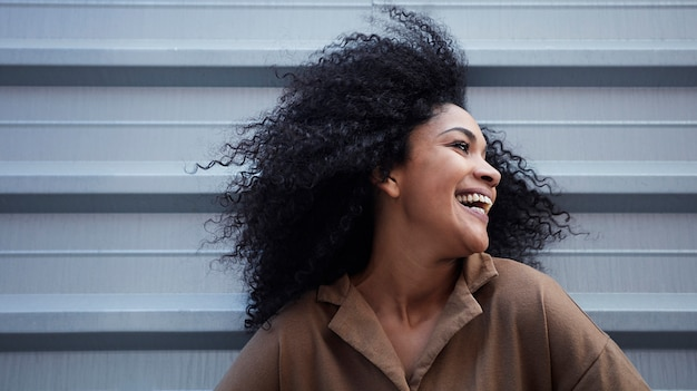 Young black woman with afro hair laughing and enjoying
