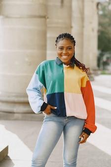 都会で笑顔のアフロ髪型の若い黒人女性。カラフルなセーターの混血の女の子。