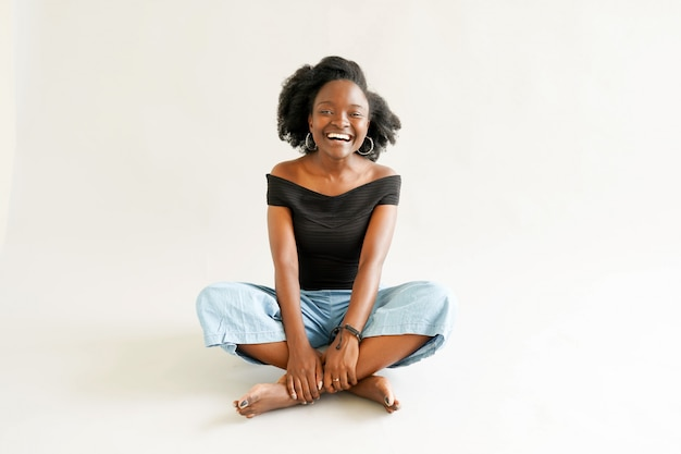 Young black woman with afro hairstyle smiling.