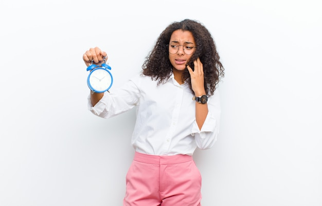 Young black woman with an alarm clock on white wall