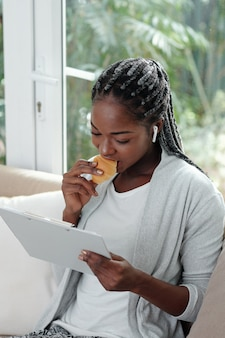 Young black woman with braided hair eating croissant when reading article in document on clipboard
