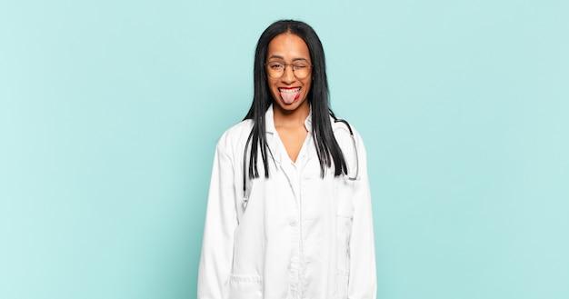 Молодая темнокожая женщина с веселым, беззаботным, бунтарским настроем, шутит и высунула язык, развлекается. концепция врача