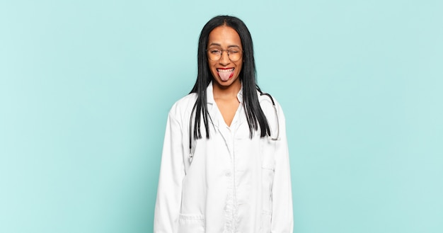 Young black woman with cheerful, carefree, rebellious attitude, joking and sticking tongue out, having fun. physician concept