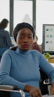 障害のある若い黒人女性、無効な、障害者の麻痺した障害者がカメラを見て欲求不満、ビジネスオフィスの部屋の車椅子に座って悲しい、チームとの金融プロジェクトで働いています。
