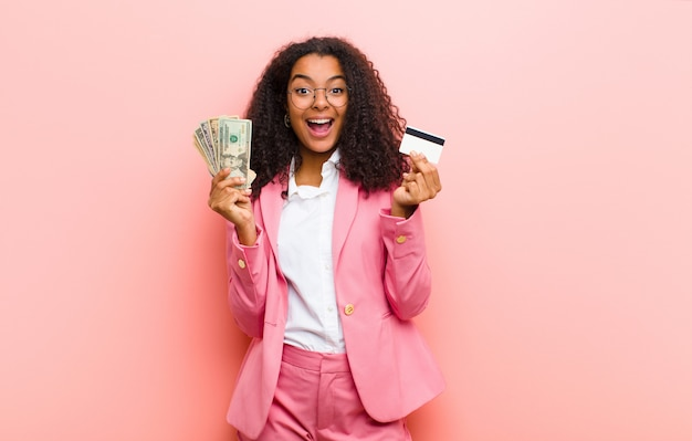 Young black woman with dollar banknotes on pink wall