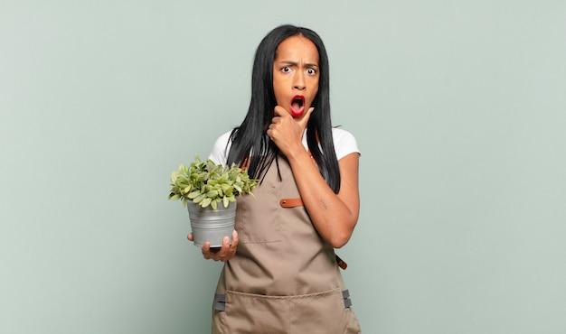 Молодая чернокожая женщина с широко открытыми глазами и ртом, положив руку на подбородок, ощущает неприятный шок, говорит что или ничего себе. концепция садовника