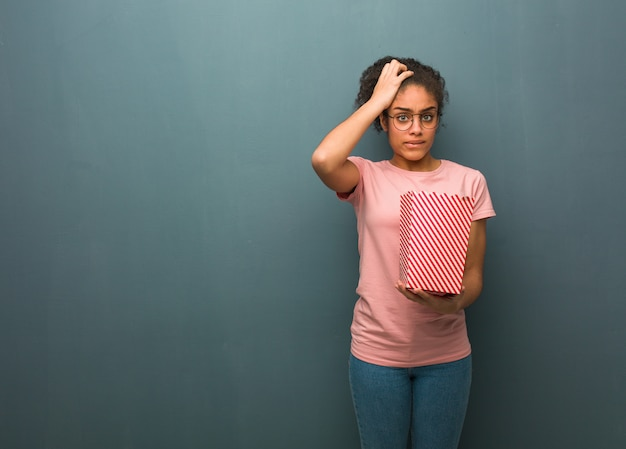 Young black woman worried and overwhelmed. she is holding a popcorns bucket.