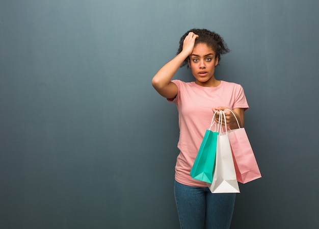 Young black woman worried and overwhelmed. she is holding a shopping bags.