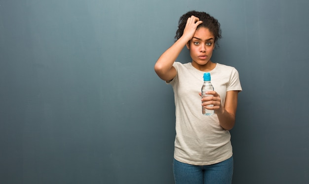 Young black woman worried and overwhelmed. she is holding a water bottle.