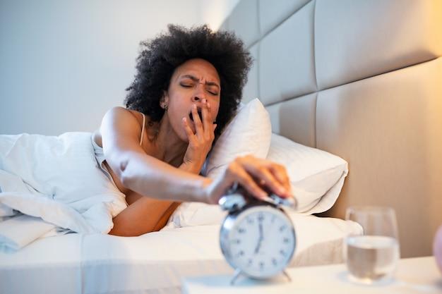 Молодая черная женщина зевок просыпается усталость бессонница, держа будильник.