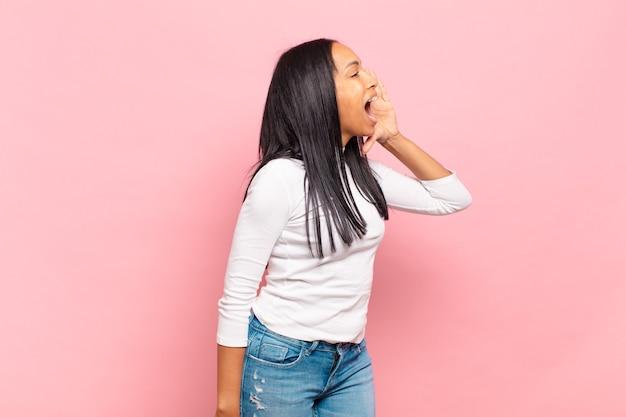 口の横に手を置いて、横のスペースをコピーするために大声で怒って叫んでいる若い黒人女性