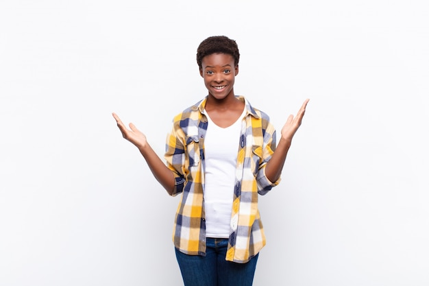 젊은 흑인 여성이 행복하고, 흥분하고, 놀랐거나, 충격을 받고, 웃고, 믿을 수없는 것에 놀랐다.