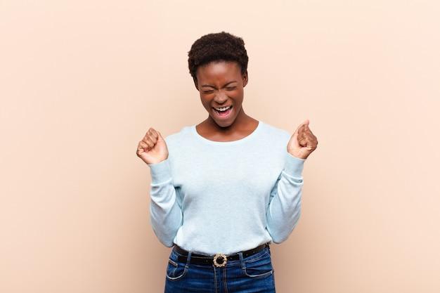 Молодая чернокожая женщина выглядит очень счастливой и удивленной, празднует успех, кричит и прыгает