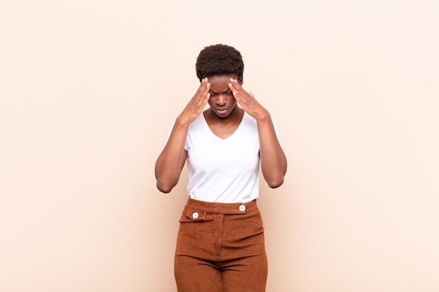 Молодая чернокожая женщина выглядит напряженной и расстроенной, работает под давлением с головной болью и обеспокоена проблемами
