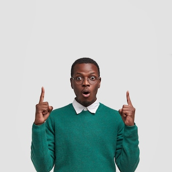 Young black young man has stupefied expression points upwards with both index fingers, has bated breath, opens mouth