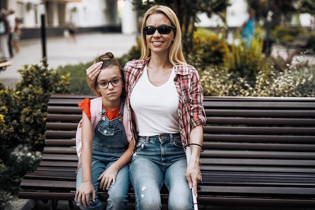 그녀의 작은 딸과 함께 학교 운동장에 앉아 젊은 시각 장애인 어머니. 그들은 웃고 함께 이야기합니다.