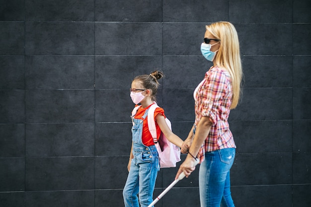 Young blind mother walking with her little daughter on city street. they wearing face protective masks. back to school and new coronavirus lifestyle concept.