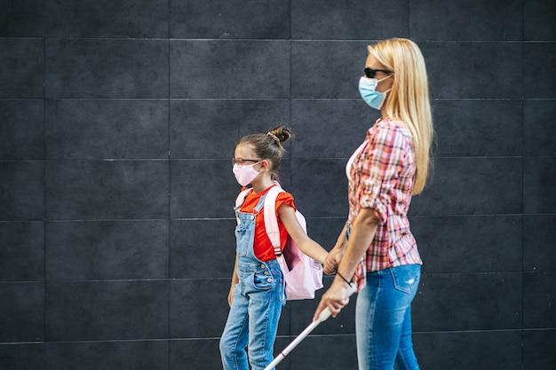 街の通りで彼女の小さな娘と一緒に歩いている若い盲目の母親。彼らは顔面保護マスクを着用しています。学校に戻って、新しいコロナウイルスのライフスタイルの概念。