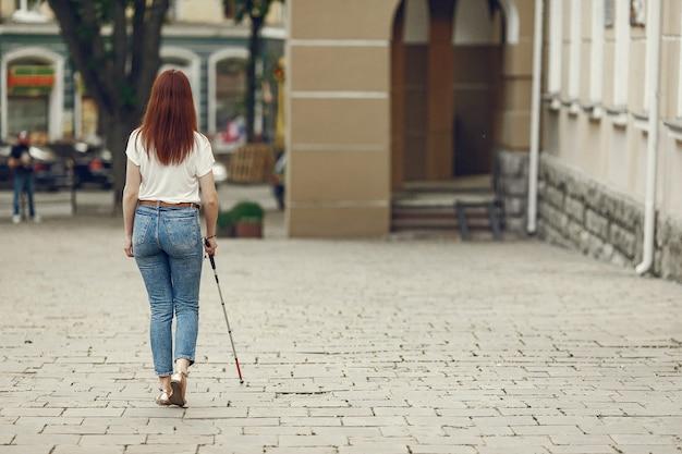 Молодой слепой человек с длинной тростью гуляет по городу