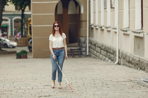 街を歩いて長い杖を持つ若い盲人