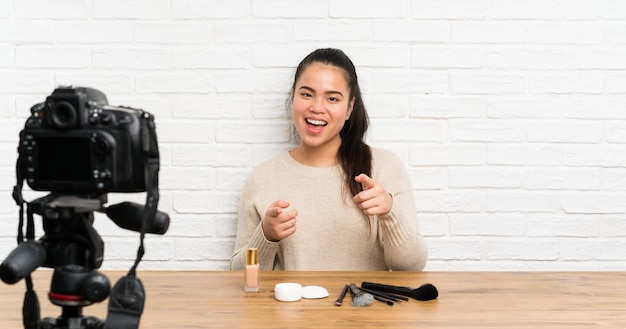 Young blogger asian girl recording a video tutorial points finger at you