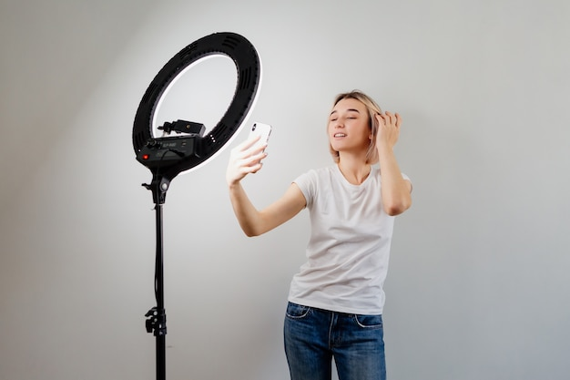 Young blogger girl is broadcasting live online at home with a ring lamp and a smartphone