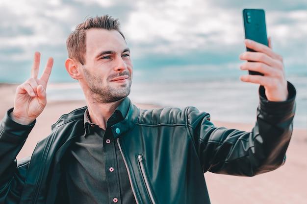 Молодой блогер, делающий селфи или потоковое видео на пляже с помощью черного смартфона.