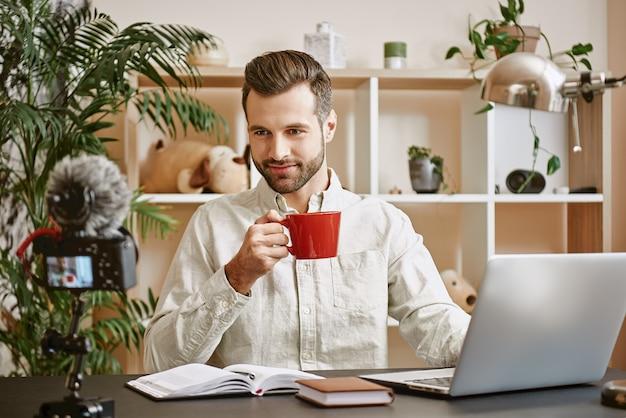 Молодой блогер-мужчина, молодой видеоблогер, записывающий видео в социальных сетях и пьющий чай, глядя на