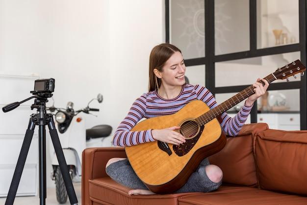 Молодой блогер играет на гитаре