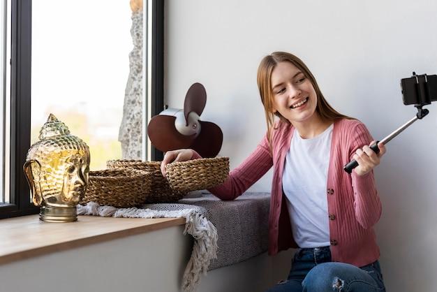 Молодой блогер записывает себя рядом с окном, показывающим домашний декор