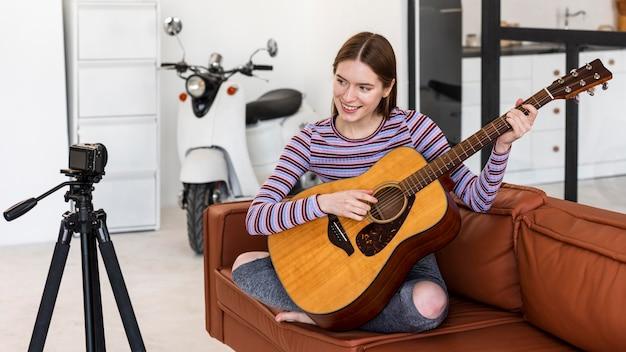 기타를 연주 자신을 녹음하는 젊은 블로거
