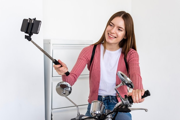 Young blogger recording herself sitting on her motorbike