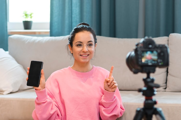 Young blogger recording herself with phone in her hand