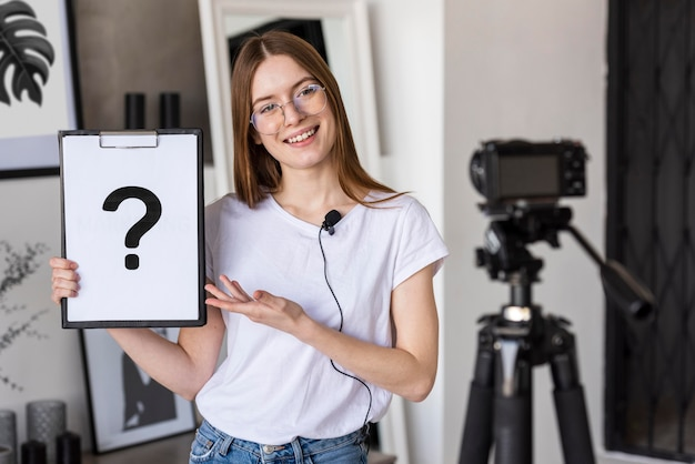 Young blogger recording with professional camera holding clipboard with question mark